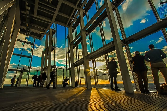 People in building with glass walls at sunset