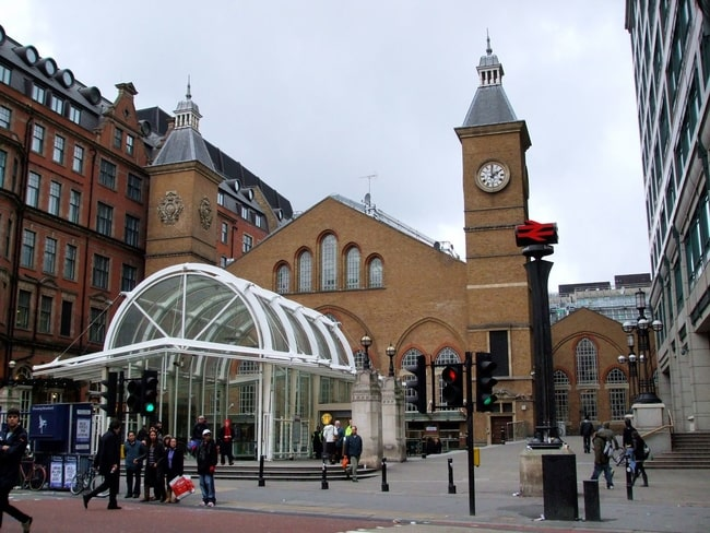 train station entrance, glass front with clock tower in background