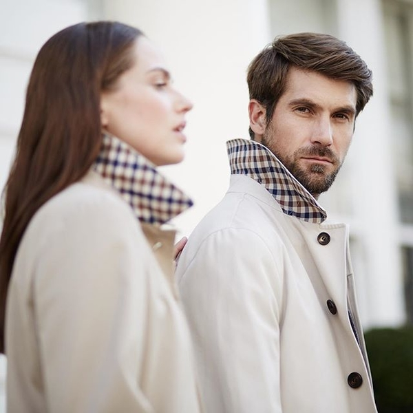 man and women in matching cream coats, man is looking at camera.