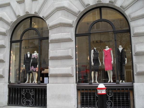 Shop windows with five dresses and L. K. Bennett printed on one window.