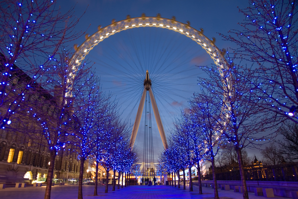 London Eye wheel in the distance, with trees covered in blue light in foreground