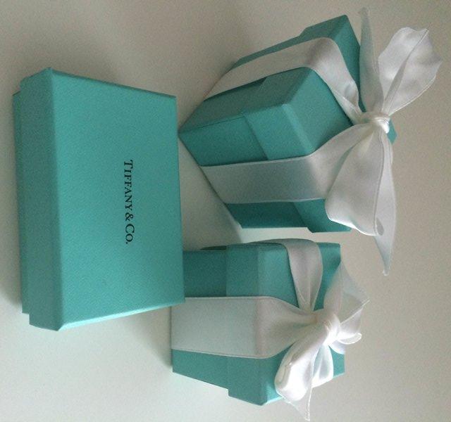 three blue boxes, front has no bow and shows Tiffany's logo. Other two have white bows.