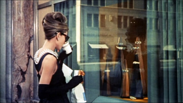 Audrey Hepburn looking at a Tiffany's window, sipping a coffee
