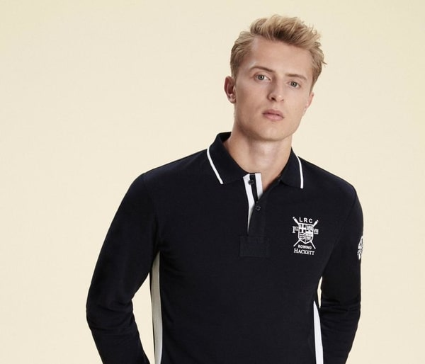 Blonde man in dark blue polo shirt with Hacknett logo
