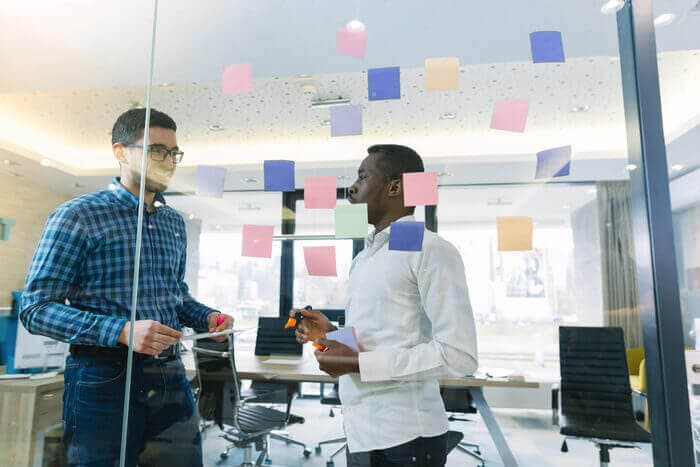 Two men talking in a modern startup office using a glass wall covered with sticky notes