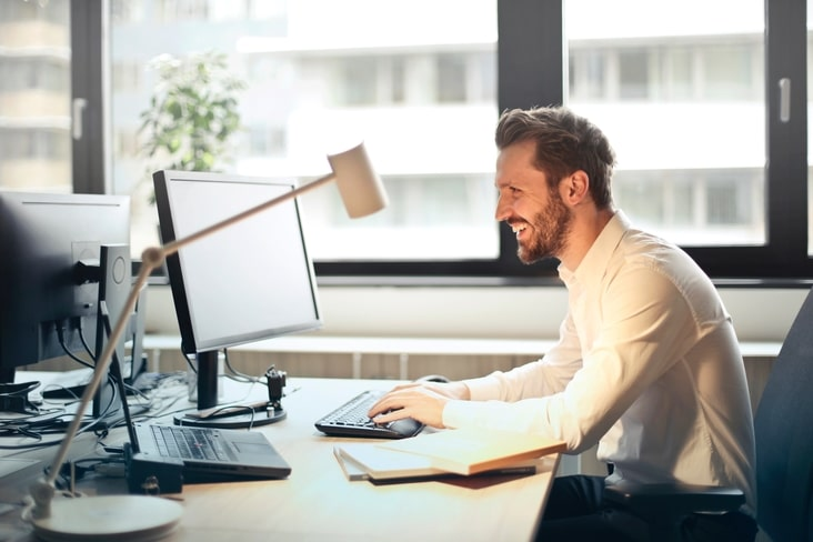 Man sat in office smiling at computer
