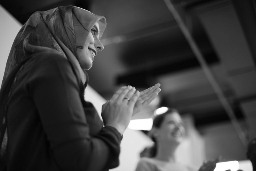 A black and white photo of a women clapping.