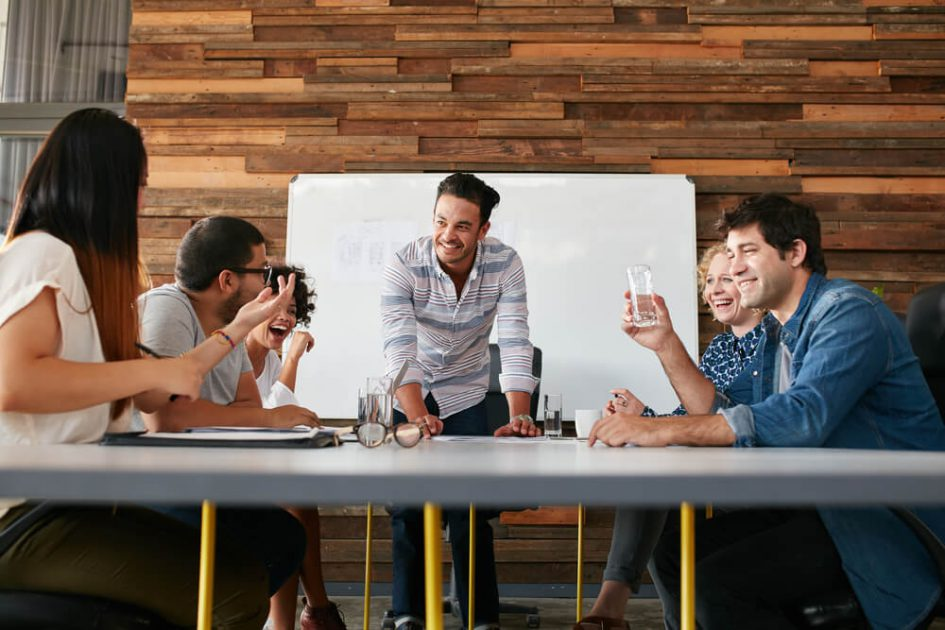 Team of men and women gathered around a table and whiteboard talking and business planning in a modern office space