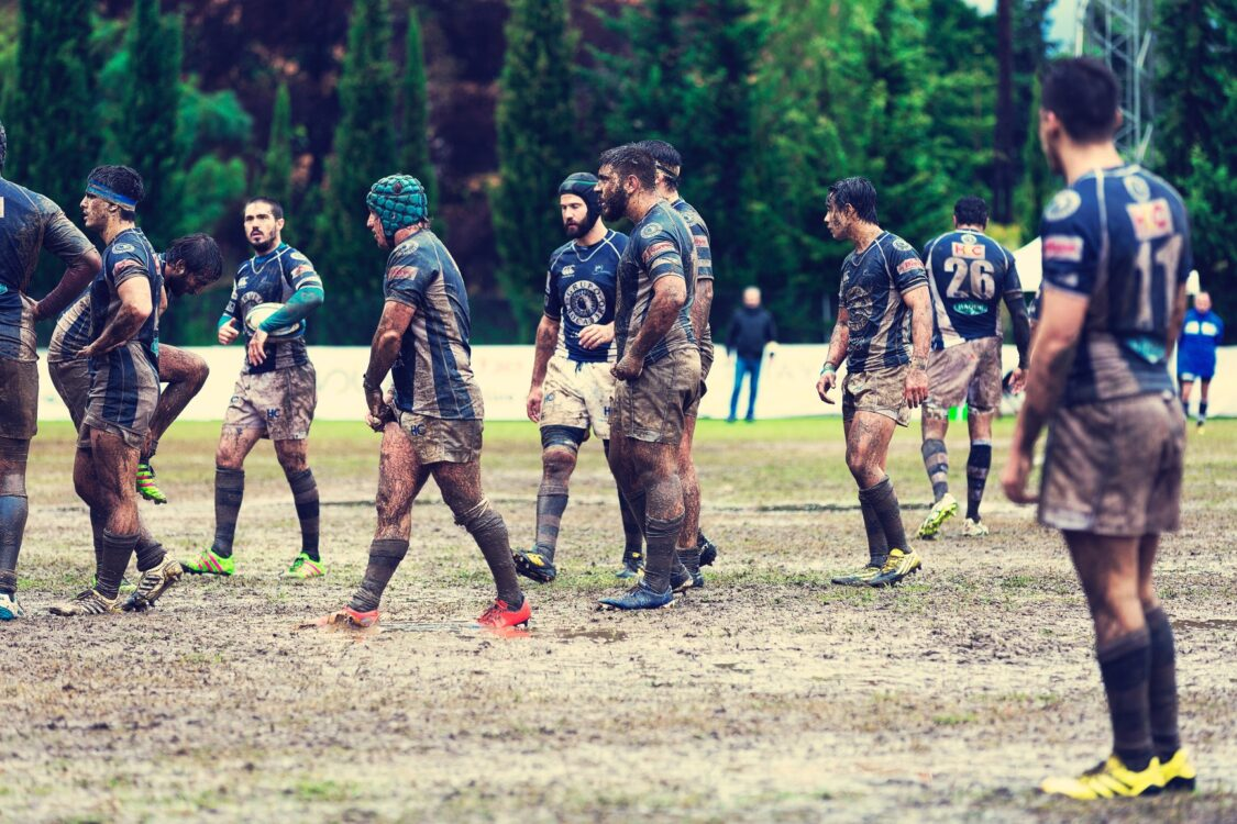 A male rugby team covered in dirt, playing rugby on a muddy field.