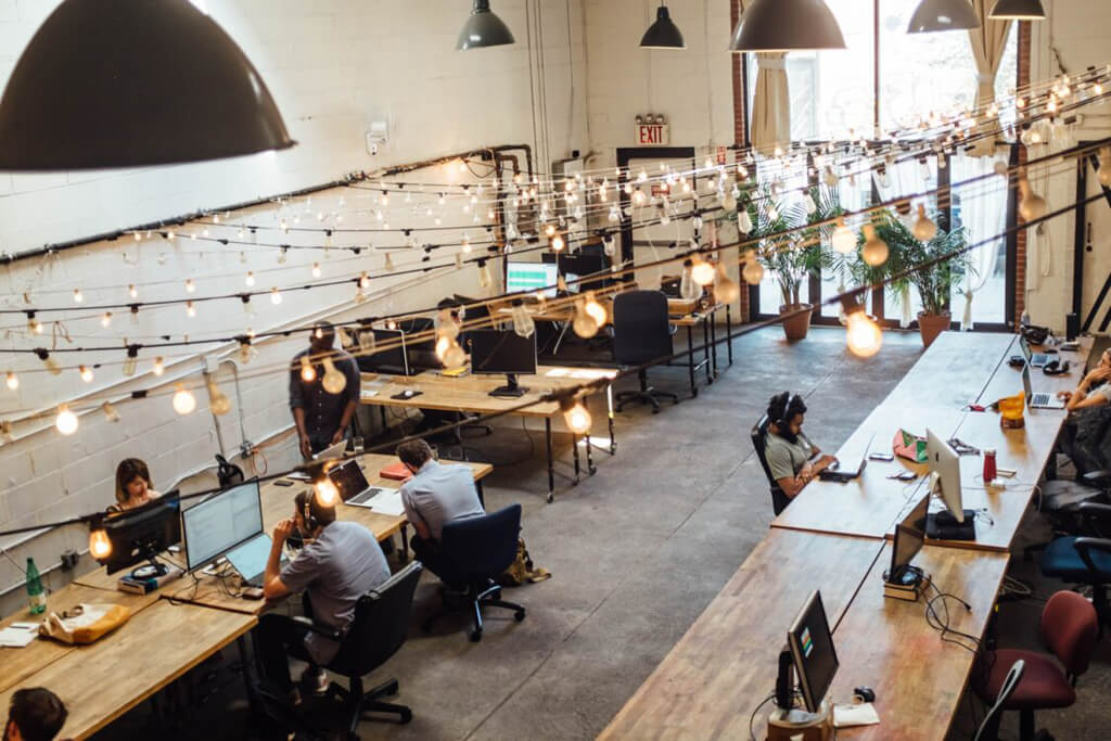 Business professionals working at large wood desks within a large open office space with large hanging lights