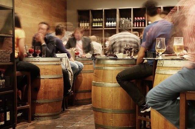 People sat around barrels, drinking in a wine bar