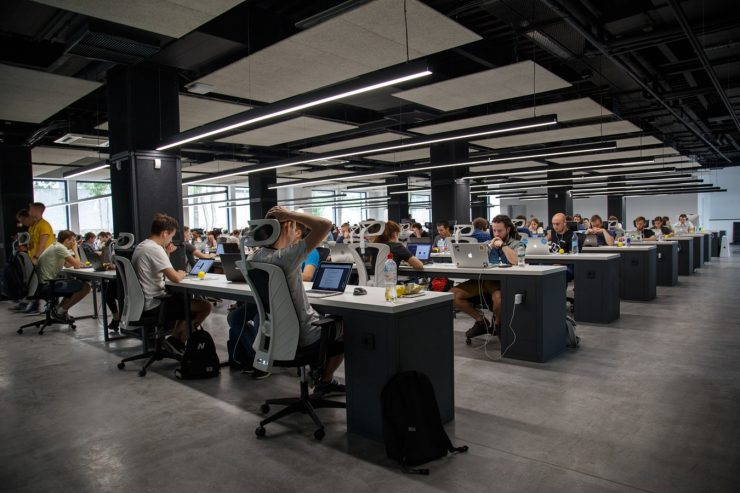 A large shared office space full of professionals working at laptops
